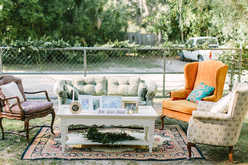 Seating areas in garden wedding reception, oriental rugs, electic chairs and couches, coffee tables