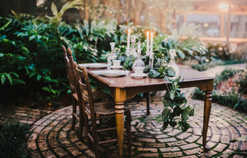 antique glass, wooden table, china and garland