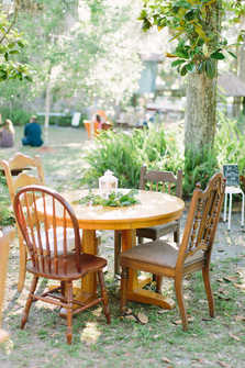 eclectic wood tables and chairs, greenery centerpieces, white lantern centerpieces