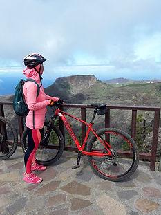 eine fahrradfahrerin guckt auf einen berg in la gomera
