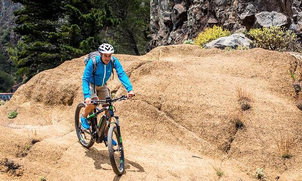 fahrradfahrer fährt steilen berg runter
