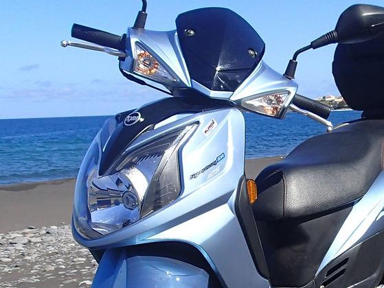 Ein Motorroller steht am Meer
