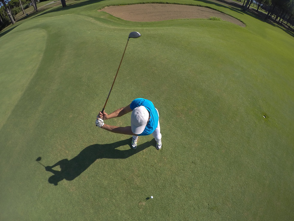 top view of golf player hitting shot wit