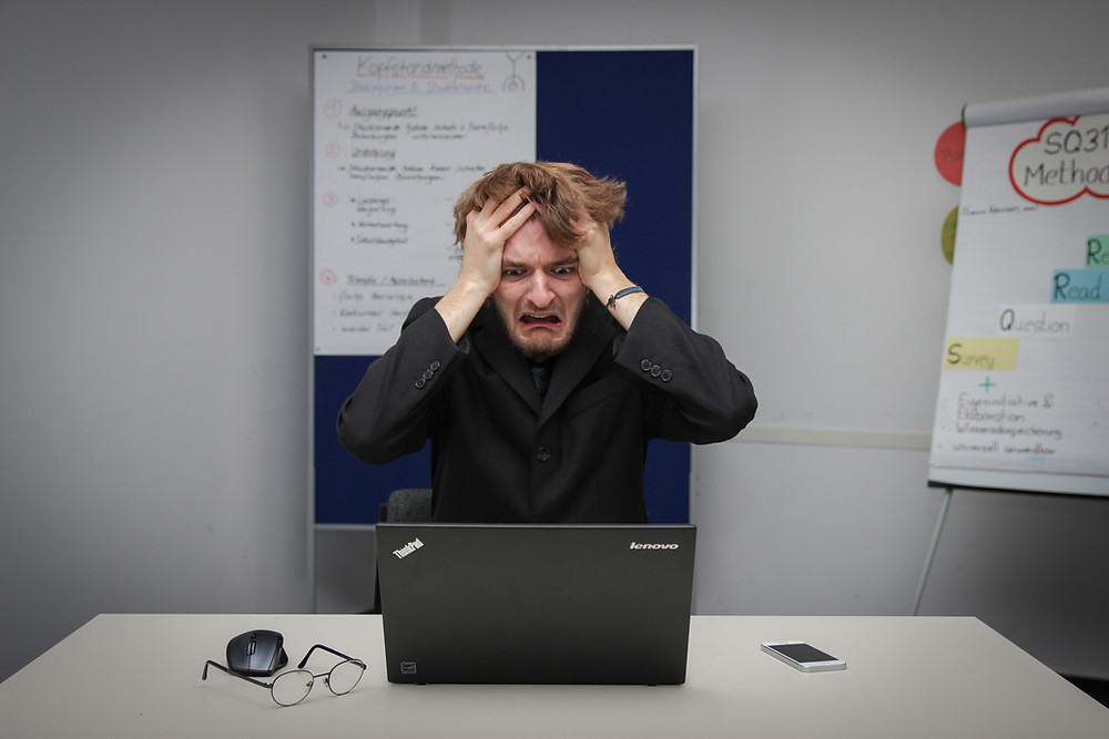 Frustrated man in front of laptop