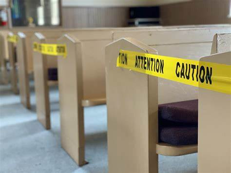 Church pews sealed with barrier tape during the COVID-19 pandemic.