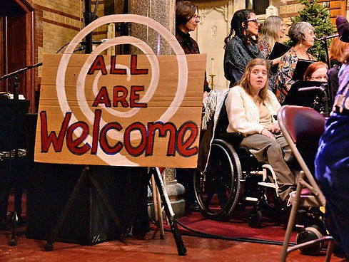 A choir of diverse singers, with large sign 'All are Welcome' next to young person in wheelchair