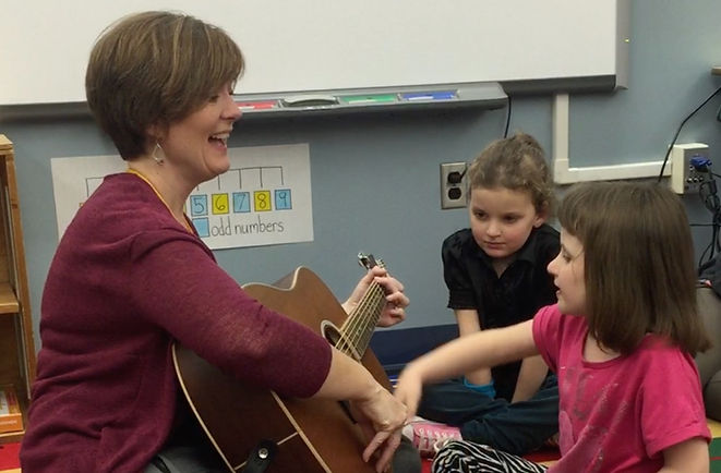 child strumming therapist's guitar with another child looking on