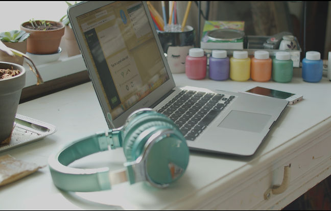 an open laptop, a smartphone and headphones on a desk with plants and paints surrounding