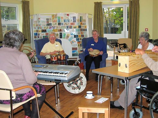 a music therapy group in hospice day care, seated in a circle playing a variety of instruments