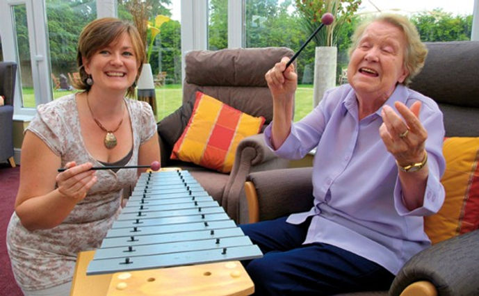 Therapist and client singing and playing the metallophone