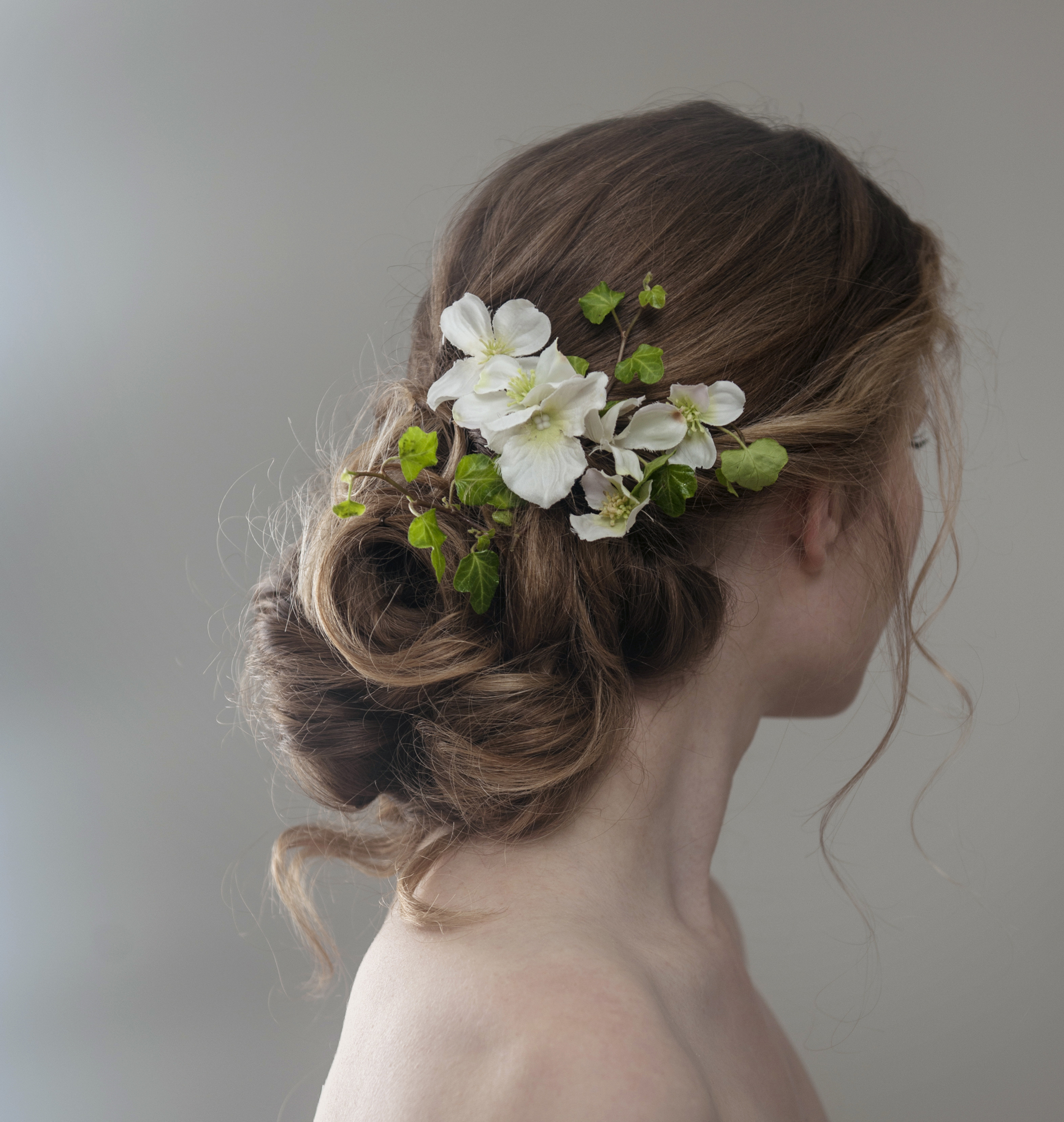 Messy low bun bridal hair with roses