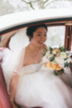 Asian bride in traditional wedding dress with bouquet of flowers getting out of wedding car to get married.
