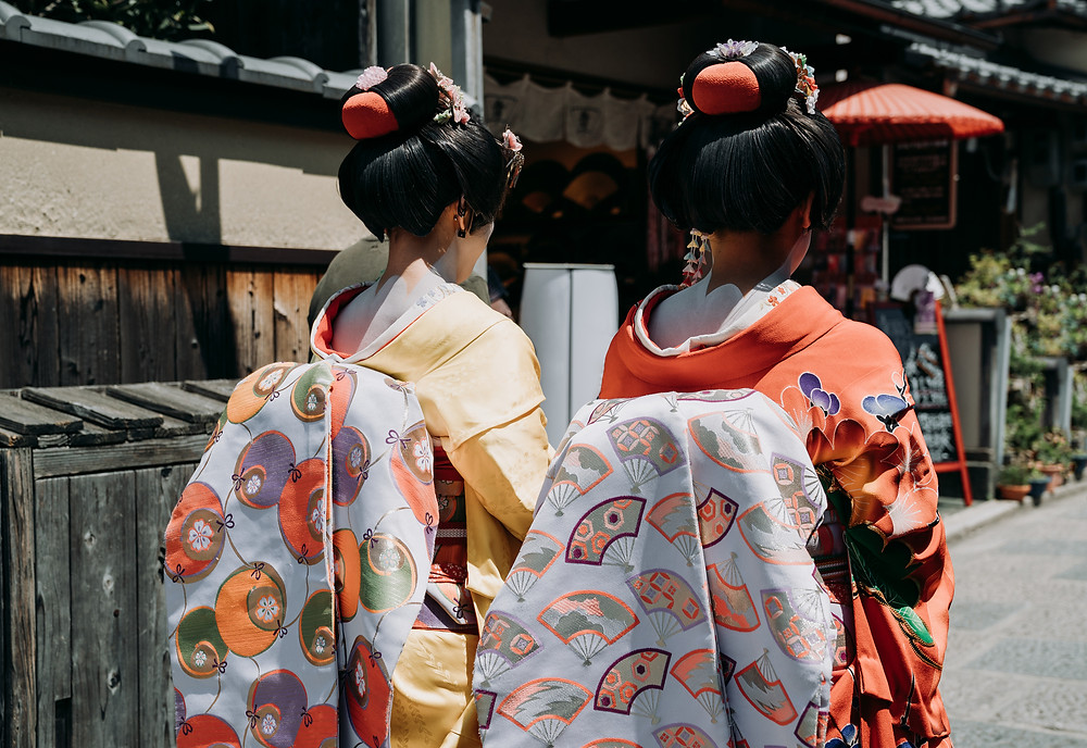 two geisha girls with white makeup walking away