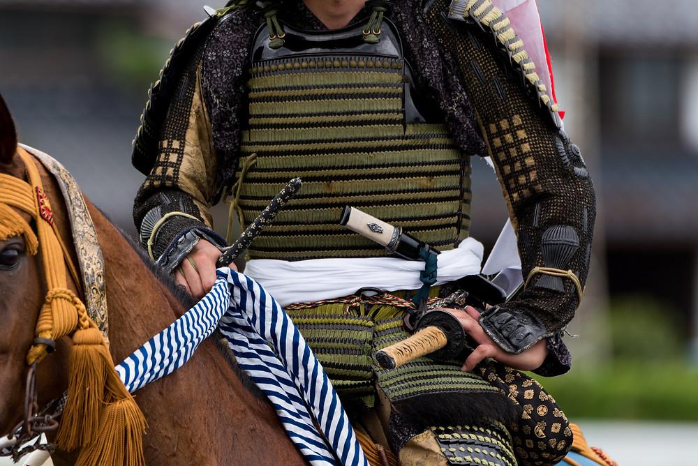 man in samurai armor riding a horse