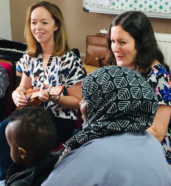 Hannah playing the ukulele and Kathryn singing and smiling with a group of adults and children
