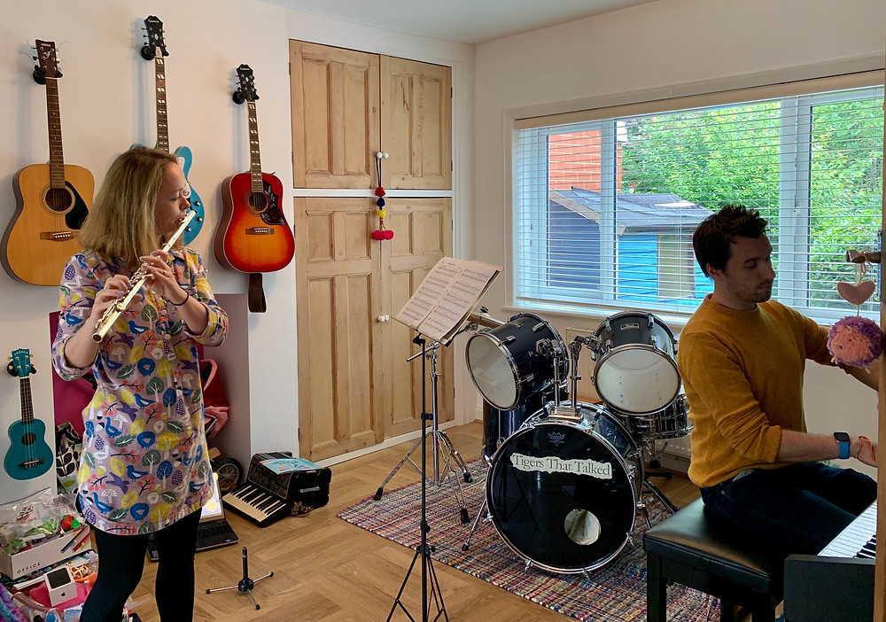 Hannah is playing the flute and Chris is playing the piano in a living room with lots of instruments in the background
