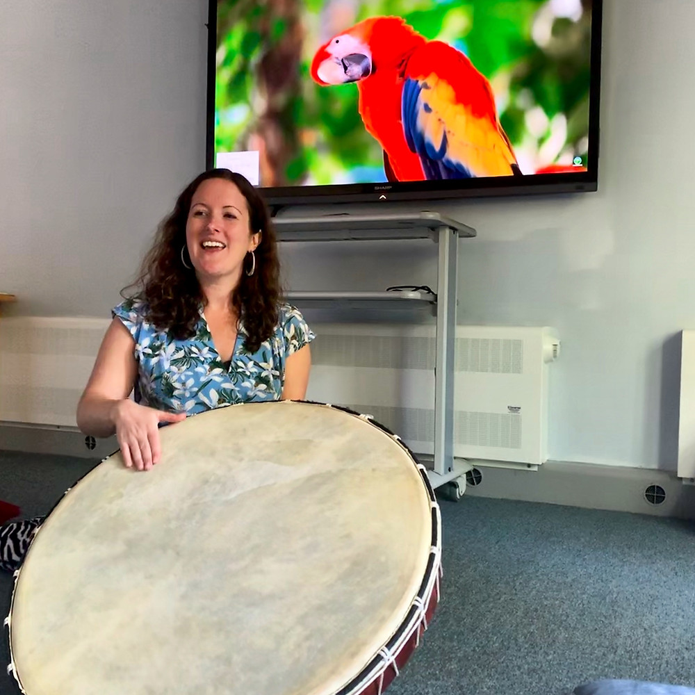 Kathryn singing and playing a large drum, with a parrot on the television in the background