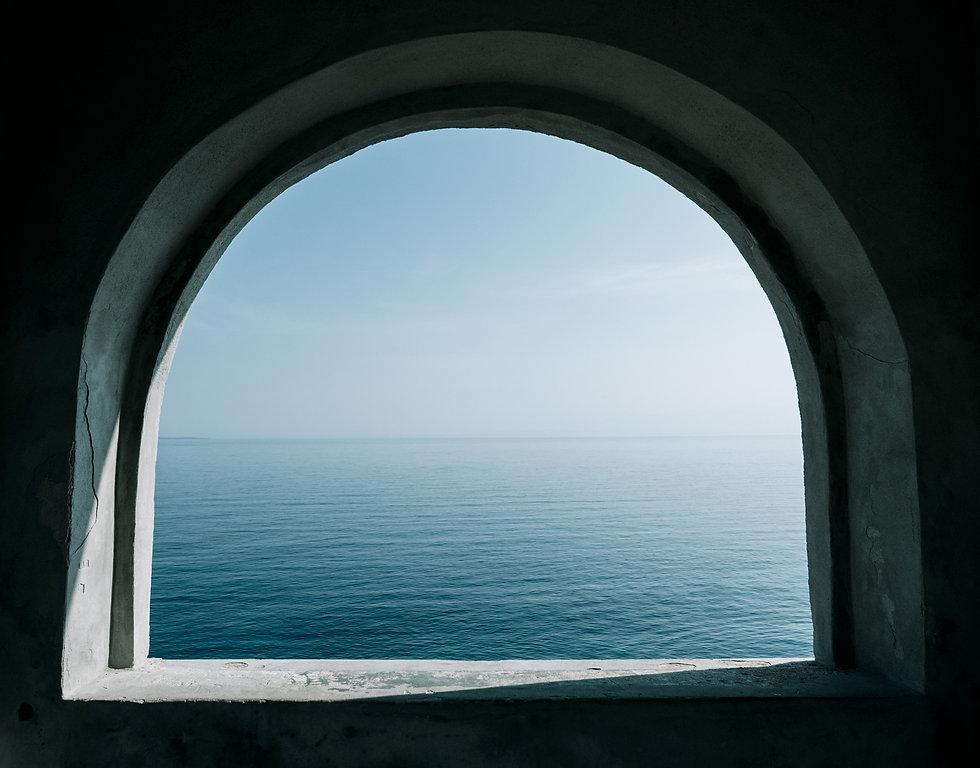 arched-window-overlooking-sea-summer-minimalism-mi-XFV7DFR.jpg