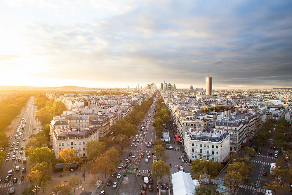 Cliché réalisé du haut de l'arc de triomphe au soleil couchant avec au loin le quartier d'affaires de La Défense.