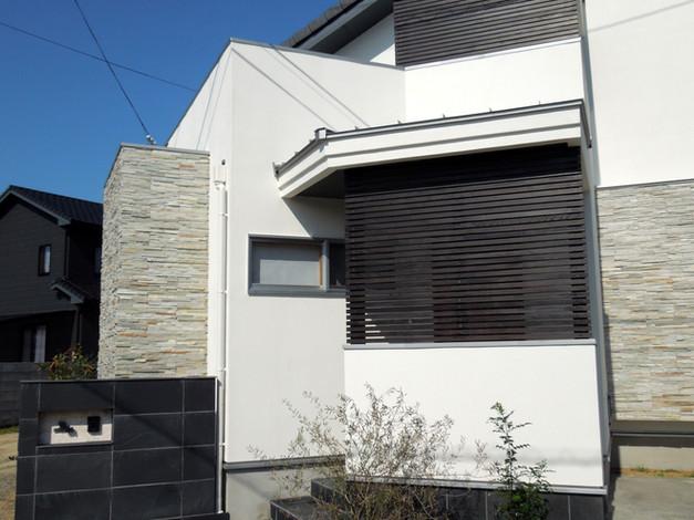 白壁と天然石の家