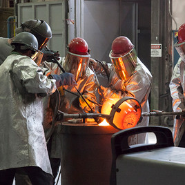 Foundry workers pouring bronze from crucible.