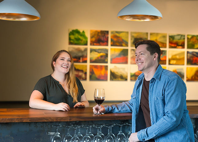 Picture of co-owners Jay and Lisa Anderson laughing at the wine bar in Walla Walla tasting room