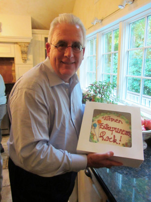 Brian Brady, one of the organizers of the UConn conference, holds an on-topic ice cream cake at the celebratory dinner following the event.