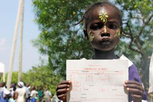 Young girl with her newly obtained documentation, at a street fair in Kenya Photo: Plan.org