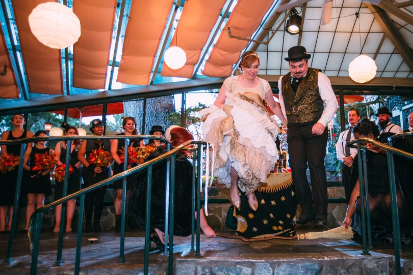 "Years later, Liza was still a pagan. Her ""Hallowedding,"" a year ago today, was conducted as a Wiccan ""hand fasting."" Here she and her new husband, AJ, both wearing steam punk versions of the traditional get up, end the ceremony by jumping over a broomstick. Their marriage brought together families of vastly different religious traditions and the use of this New Age approach actually smoothed over all that quite nicely. Well, except for Liza's father's rather strait-laced New York contingent. To see the shocked look on those faces, I would have jumped over 50 broomsticks."