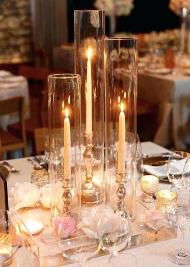 Candlesticks in cylinder glass centerpieces
