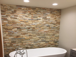 Stacked stone wall, clawfoot tub