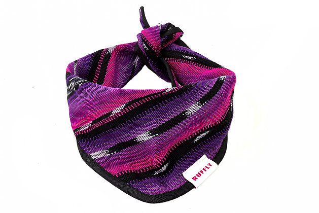 Handwoven dog bandana with pink, purple, and black pattern and black piping