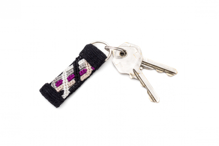 Handmade knotted keychain in purple and black handwoven fabric with key