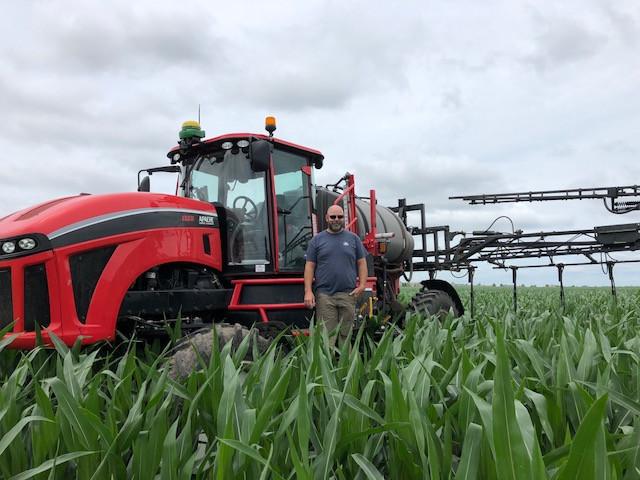 Dean Atkins shown by his applicator last week in a field east of Bloomington-Normal / CIFN photo.