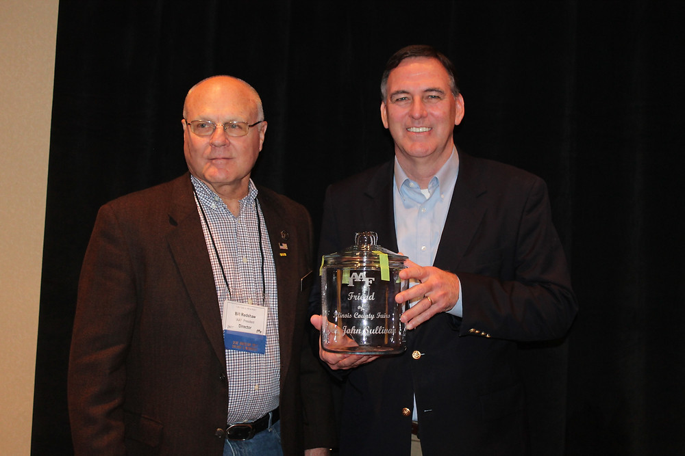 John Sullivan, right, is honored by Bill Redshaw of the IL Assn. of Ag Fairs in 2017 / CIFN file photo