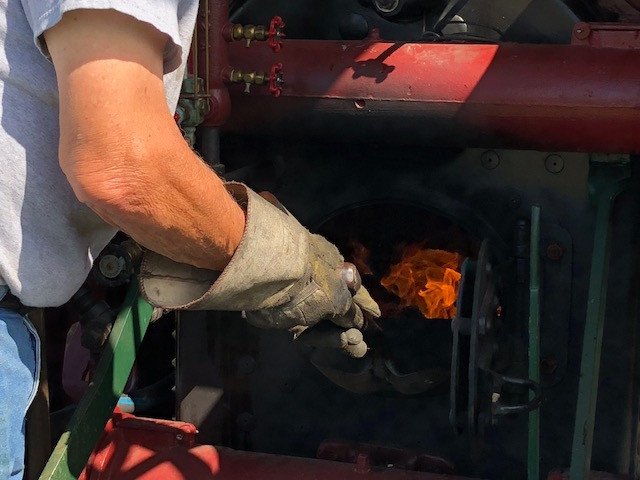Dick Smith of Gridley puts more coal in his steam engine at the Threshermen's Reunion this week / CIFN photo.