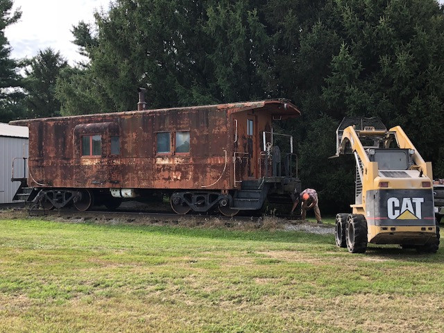 Andrew Navis with Ruff Brothers grain helps to haul away a train caboose near Fairbury this week / CIFN photo.