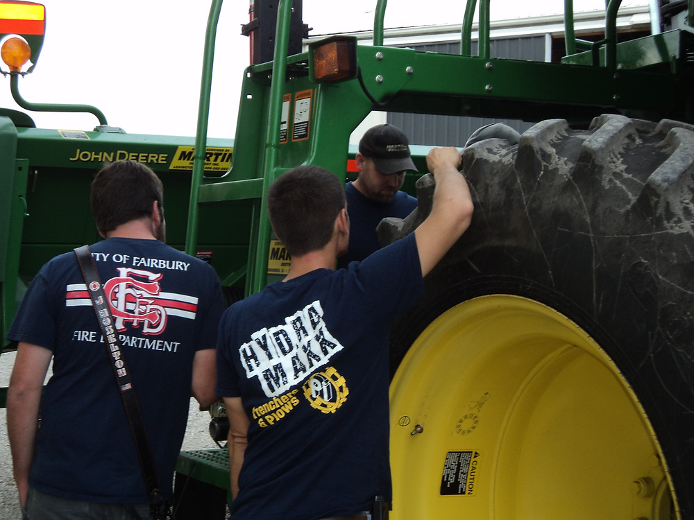 Mark Brown (back) shows members of the Fairbury Fire Dept. what to look for in case of a combine fire / CIFN photo.