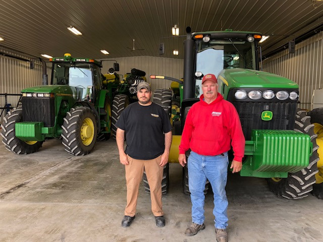 Aaron (left) and Steve Ricketts pose among their tractors north of Fairbury last week / CIFN photo.