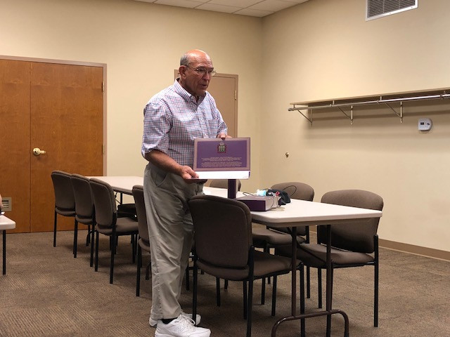Ray Hankes displays a Russian candy package before members of the Fairbury Rotary Club / CIFN photo.