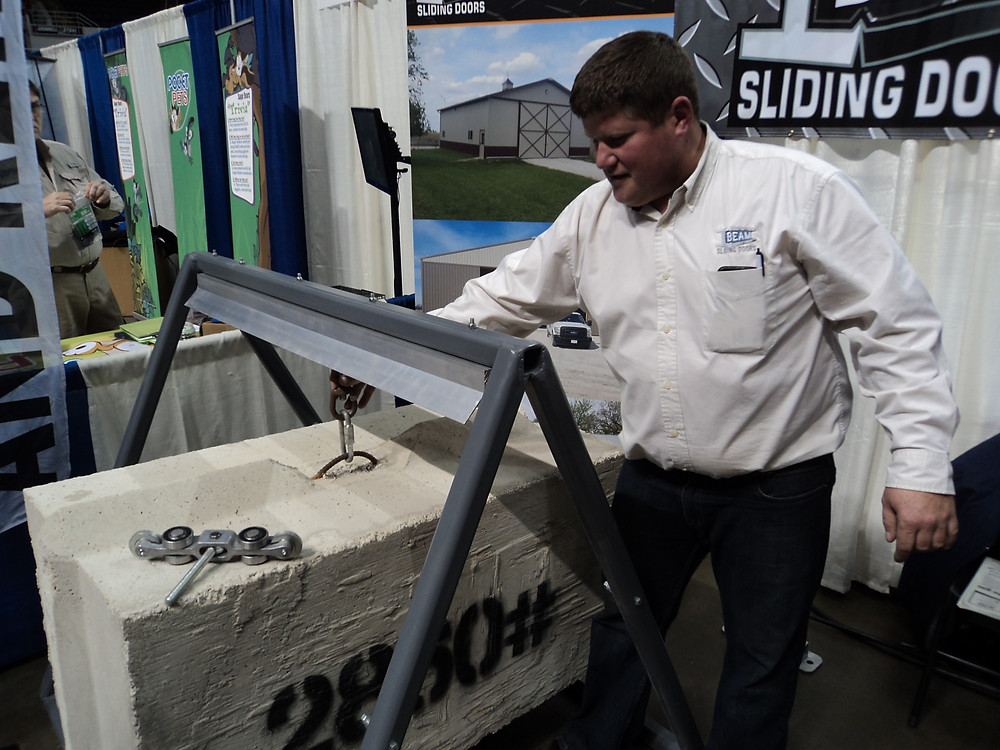 Jon Fehr demonstrates his ultra-glide door system at the Greater Peoria Farm Show on Thursday / CIFN photo.
