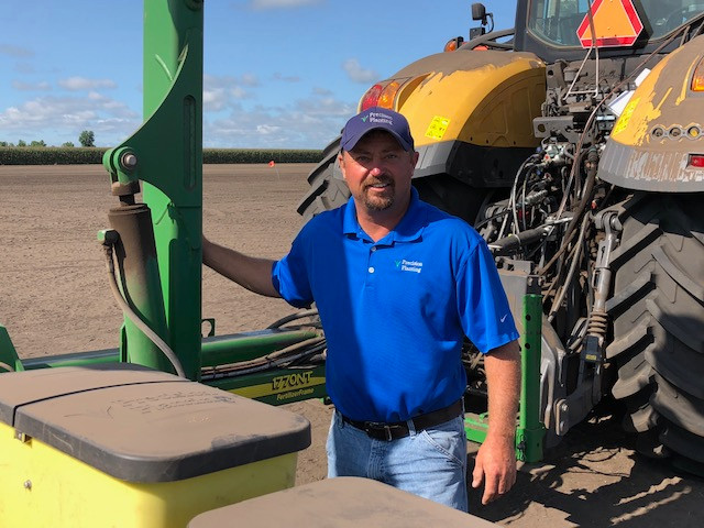 Precision Planting's Jason Webster poses near a tractor at the company's PTI Farm at Pontiac over the summer / CIFN photo.