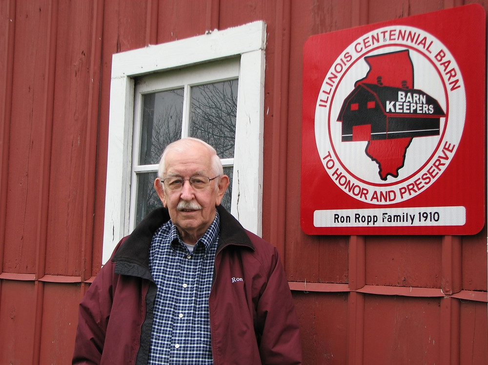 Ron Ropp is pictured here on his family's Dry Grove Township farm. Ron is standing next to a century old barn that now features a handsome and durable Illinois Centennial Barn sign. (photo provided)