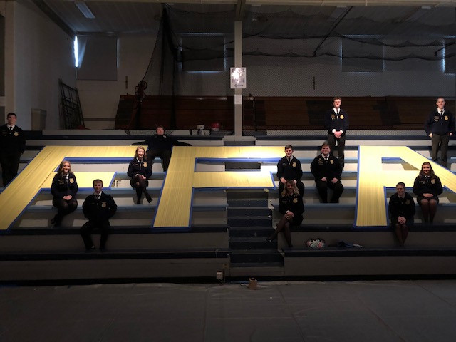 Cissna Park FFA members sit near a sign they made for Friday night's FFA banquet / CIFN photo.