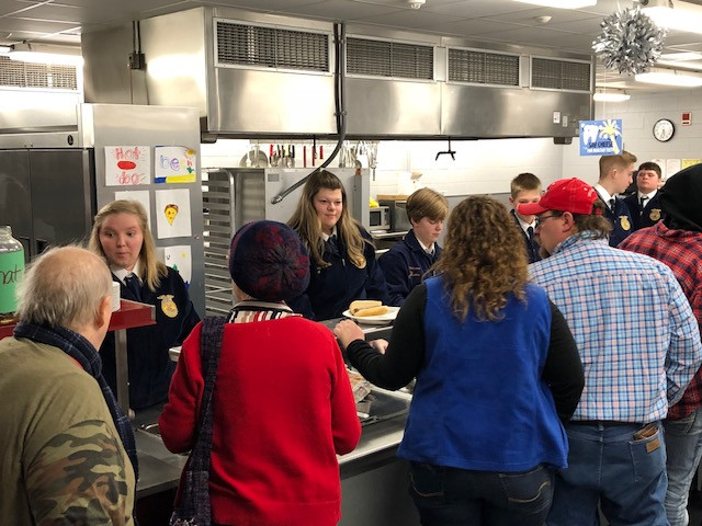 Local folks are served dinner at the Lexington FFA auction fundraiser Saturday night / CIFN photo.