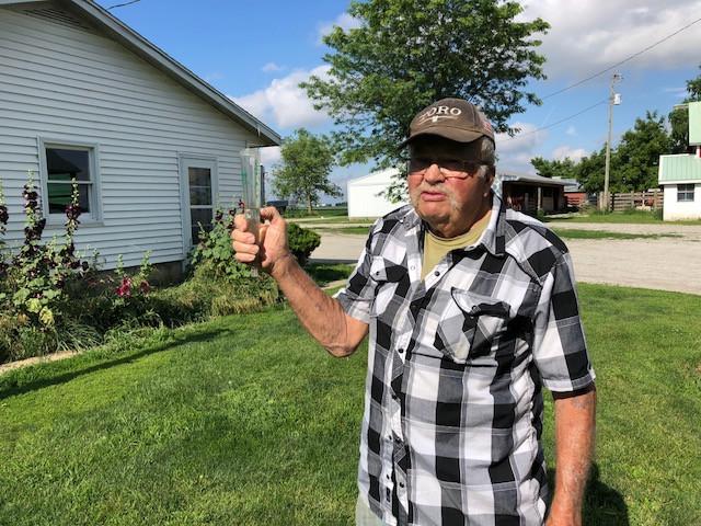 Jon Goembel checks the rain gauge on his Livingston County farm last week / CIFN photo.