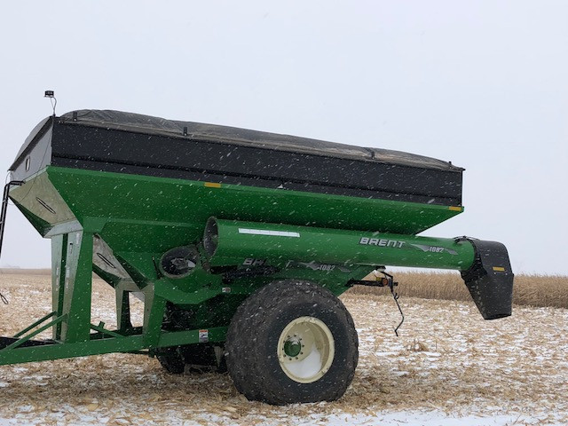 An auger wagon sits in a snowy field Monday afternoon / CIFN photo.