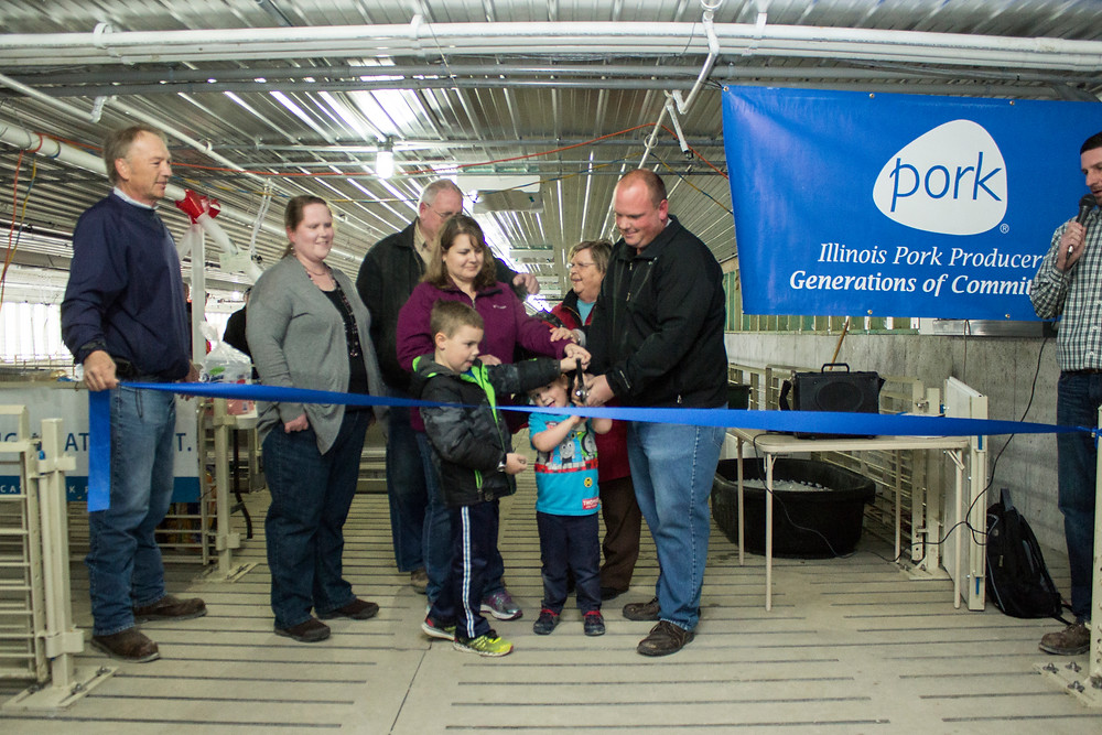 Nic Anderson of the ILDG, left, assists as the Clark family cuts the ribbon symbolizing the opening of their two new hog barns. From left: Dianne Trimble, Carl's sister, Jody Clark, sons Caleb and Lucas, and Carl Clark.  Photo from: IPPA
