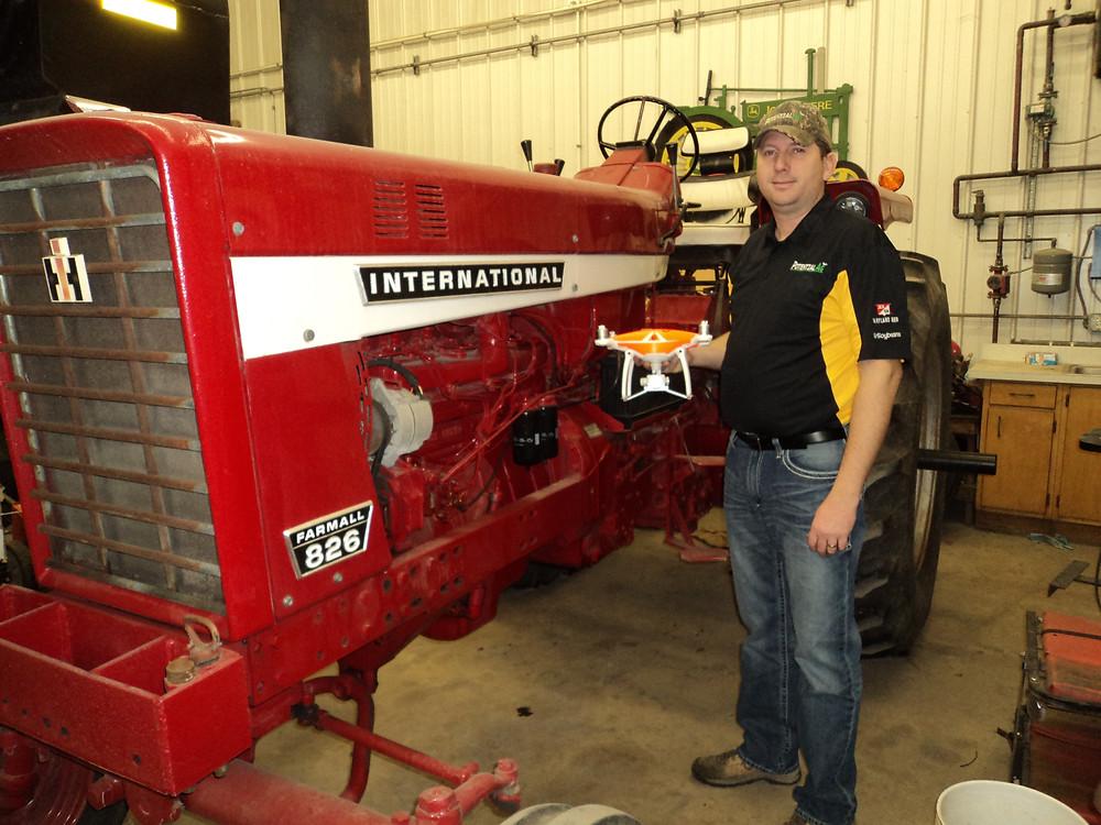 Matt Boucher poses in his shop with his Farmall 826 / CIFN photo.