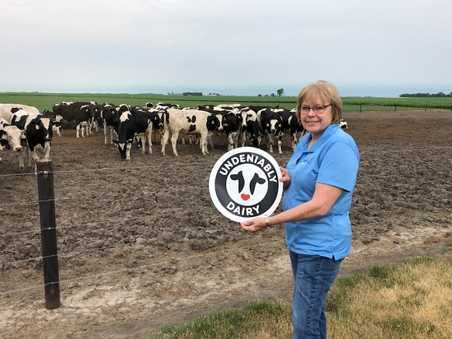 Marla Behrends of Midwest Dairy poses with the new Undeniably Dairy logo last week / CIFN photo.